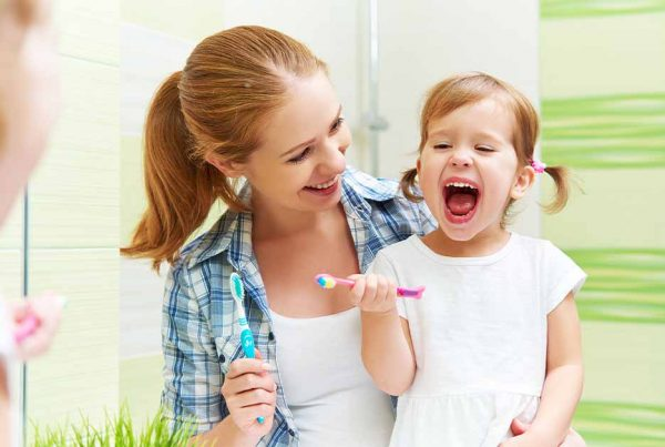mother maintains healthy teeth for her child girl
